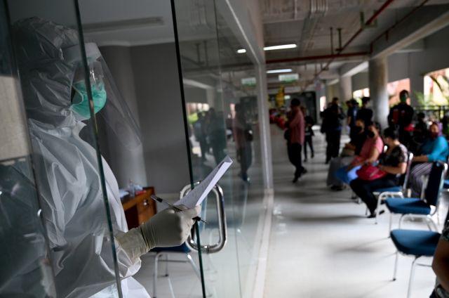 Un trabajador médico que usa equipo de protección llama por su nombre de una persona que espera para hacerse la prueba del coronavirus COVID-19, en un mercado tradicional en Denpasar, la isla turística de Indonesia en Bali, el 6 de junio de 2020. (Foto de SONNY TUMBELAKA / AFP )